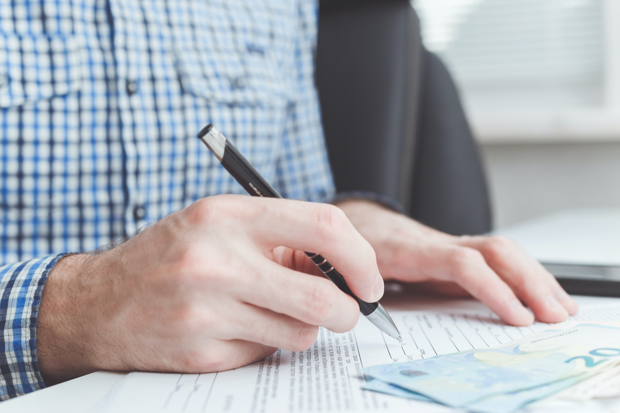 Man signing contract at office table